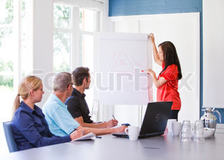 Business people having a meeting/ conference using a whiteboard and a laptop to explain the topics.