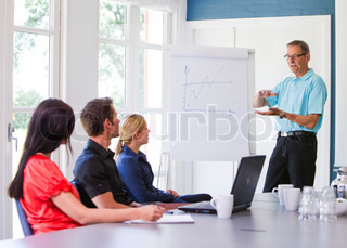 Business people having a meeting. One of them is explaining the goals for the next period.  Business people having a meeting/ conference using a whit