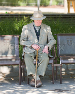 An elderly man with a cane sitting on a park bench