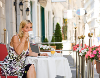 A caucasian woman drinking coffee  on a cafe in Vienna