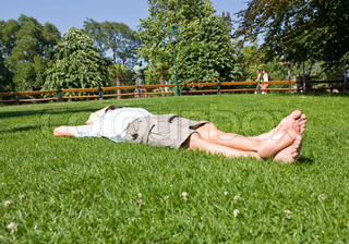 A man in shorts relaxing on a lawn on a summer day