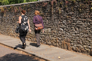 The two ladies going to their job along the wall at the foot path in summertime.