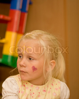 A young girl with heart painted on her face