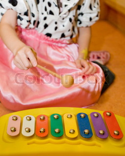 Cropped image of a girl playing xylophone