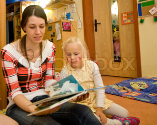 A kindergarten teacher reads a book to a young girl