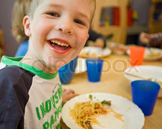 A smiling young boy eats spaghetti for lunch