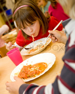 A young girl eating spaghetti