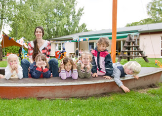 Children in kindergarten playground and their teacher
