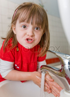 A girl makes funny face while washing her hands