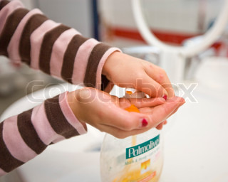 Cropped image of a young girl's hands with liquid soap