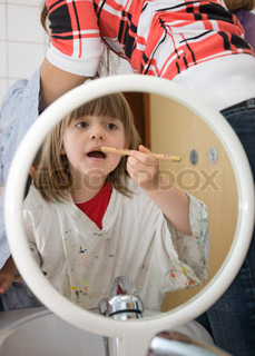 A girl looks on a mirror while painting her face