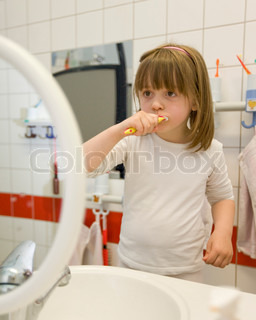 A young girl brushes her teeth