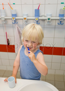 A young boy brushes his teeth