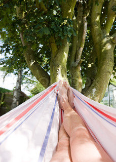 Cropped image of a man's legs relaxing on a hammock