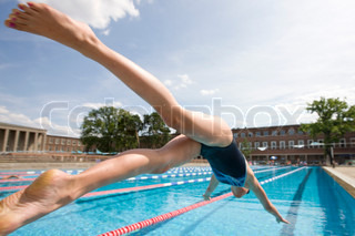 Teenage girl diving into a swimming pool