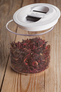 red hibiscus flower tea in the pot on a wooden board