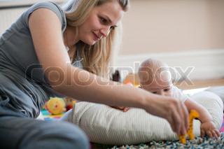 A young mother plays with her baby boy  on the floor