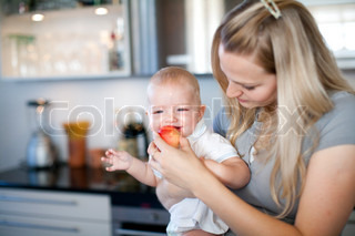 A young mother feeding her baby with an apple