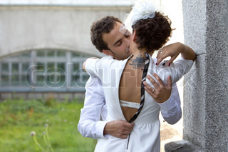 Bride with a tattoo kisses the groom. Wedding theme. The groom kisses the bride wearing in a sheath dress and hat with veil.