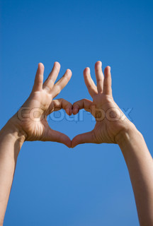 Heart shaped hands over the blue skies