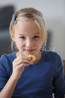 A young girl eating christmas cookie