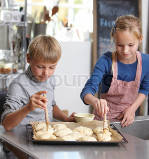 A boy and a girl making fresh buns