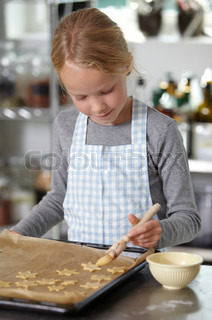 A girl brushing cookies with egg-wash