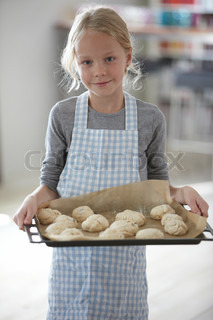 A girl holding a tray of buns