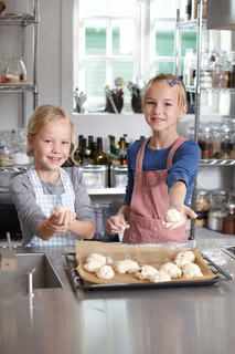 Two girls holding buns ready for baking