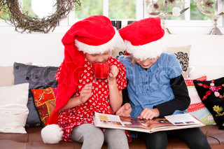 Two sisters reading a book on Christmas holiday