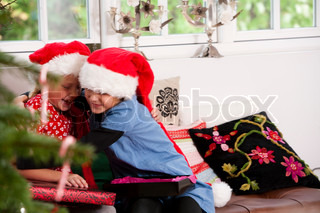 A young girl embracing her young sister on Christmas day