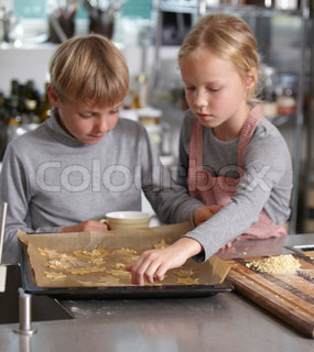 Children helping each other to make cookies