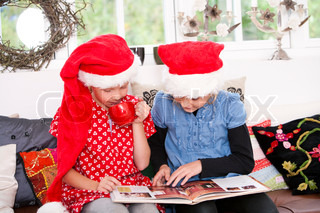 Two young girls reading a book on Christmas holiday