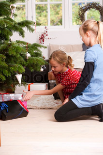 Two young girls putting Christmas presents under the Christmas tree