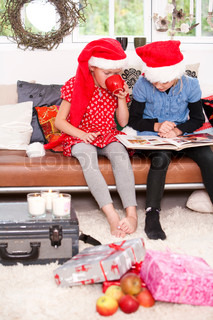Two young caucasian girls reading a book on Christmas day