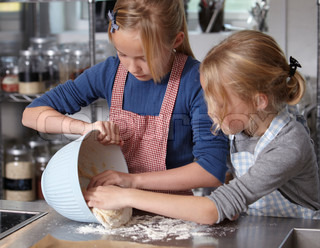 Two caucasian girls making dough for making buns