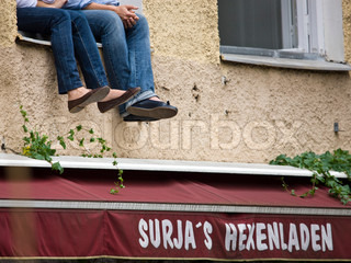 Cropped image of young people sitting on a window