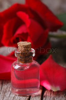 fragrant rose oil in a bottle on a wooden table vertical