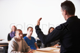 A school professor lecturing his students in a university auditorium