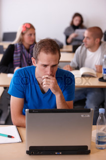 A male college student looking at his laptop