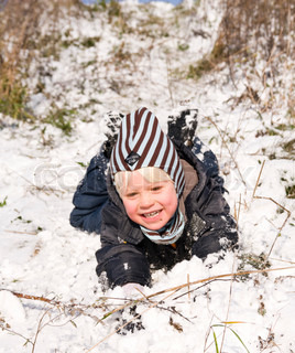 A smiling boy playing with snow on the ground