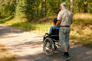 senior man pushing old disabled woman in wheelchair on small road in forest in summer