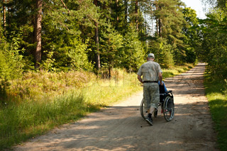 senior man taking old disable lady in wheelchair on refreshing tour in sunny forest in summer