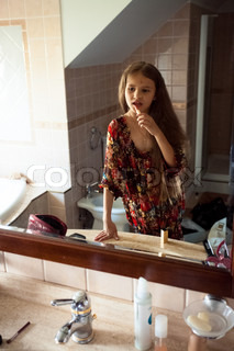 cute girl looking at mirror and painting lips with red lipstick