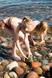 Two girls collecting stones from the beach