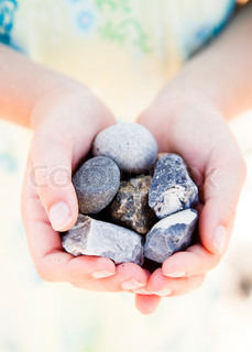 A girl holding a bunch of stones