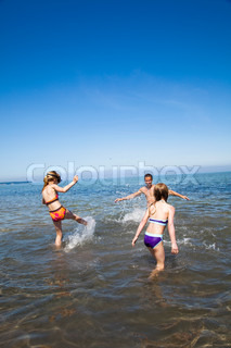 Two girls and their father in the beach