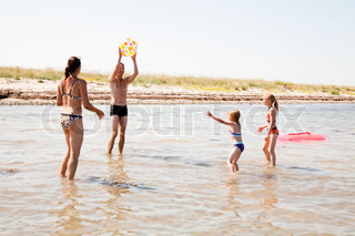 A caucasian family playing with beach ball