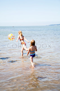 Caucasian girls playing with beach balll