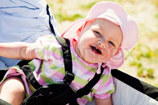 A baby girl with a summer hat sitting in a pram